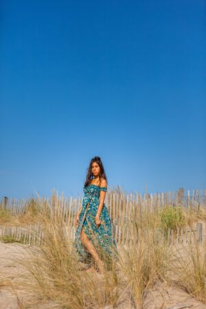 Free happy woman enjoying sun on vacations in dunes.Concept of happiness, enjoyment and well being. Sea, sand and sun. 版權商用圖片