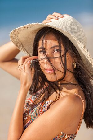 Portrait fashion of pretty young woman with straw hat on a beach. Happy Smiling girl. 版權商用圖片
