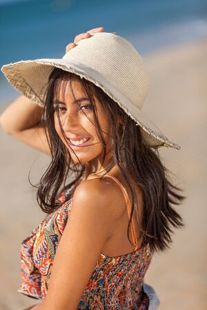 Portrait fashion of pretty young woman with straw hat on a beach. Happy Smiling girl. Stock Photo