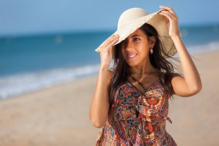 Portrait fashion of pretty young woman with straw hat on a beach. Happy Smiling girl.