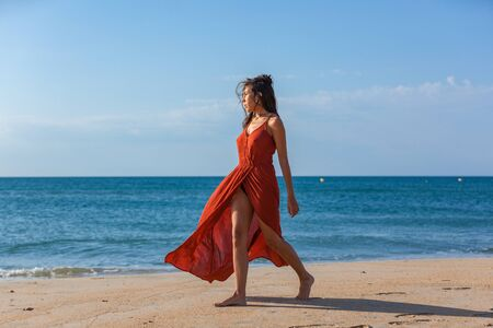 Young woman walking nude foots on the sand of the beach. Joy and freedom concept.