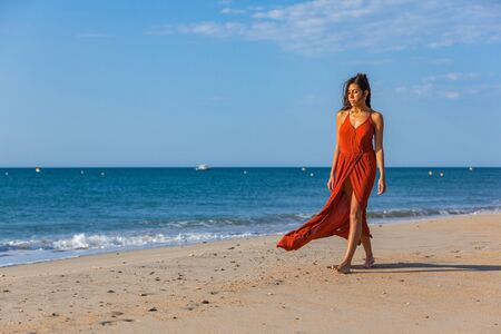 Young woman walking foots on the sand of the beach. Joy and freedom concept.
