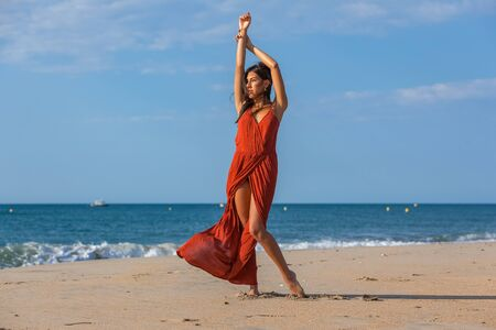 Pretty young woman in a red dress and foots on the sand of the beach. Happy girl enjoying freedom at the sea.