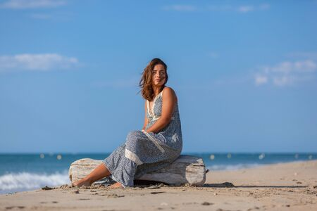 Young woman sitting on driftwood on the beach. Happiness Lifestyle Concept.