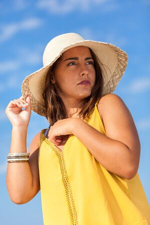 Portrait fashion of pretty young woman with straw hat on a beach in Summer. Happy Smiling girl.