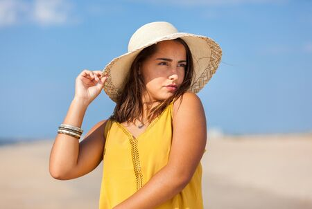 Portrait fashion of pretty young woman with straw hat on a beach in Summer. Happy Smiling girl. 版權商用圖片