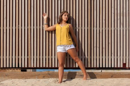 Pretty young woman leaning against a wooden fence.Happy girl enjoying freedom in the sun at the beach.