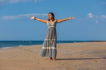 Pretty young woman in a dress and nude foots on the sand of the beach. Happy girl enjoying freedom at the sea. 版權商用圖片
