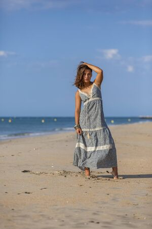 Pretty young woman in a dress and foots on the sand of the beach. Happy girl enjoying freedom at the sea.