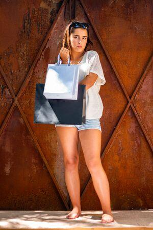 Fashion, beautiful young woman enjoying shopping in summer, holding shopping bags. Lifestyle concept.