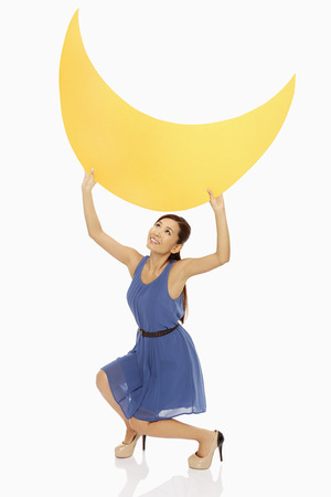Cheerful woman lifting up a yellow crescent moon Stock Photo - 22570748