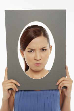 making faces: Donna che fa le facce alla telecamera, guardando arrabbiato
