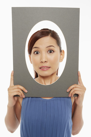 widening: Woman making faces at the camera, looking scared Stock Photo