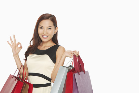 Woman with shopping bags showing hand gesture photo