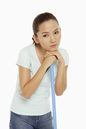 Woman resting her chin on a mop photo