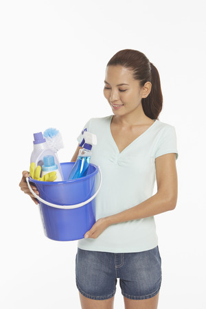 cleaning supplies: Woman holding a bucket filled with cleaning supplies