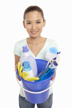 Woman holding a bucket filled with cleaning supplies photo