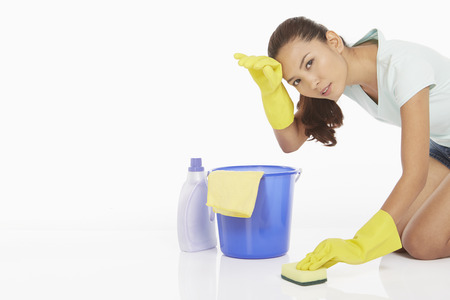 Woman scrubbing the floor, feeling exhausted photo