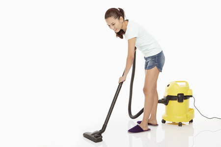 Woman cleaning and vacuuming the floor
