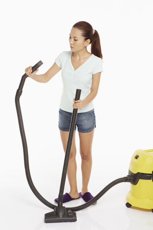 attaching: Woman attaching the grip of a vacuum cleaner Stock Photo