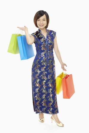 Cheerful woman in traditional clothing carrying paper bags photo