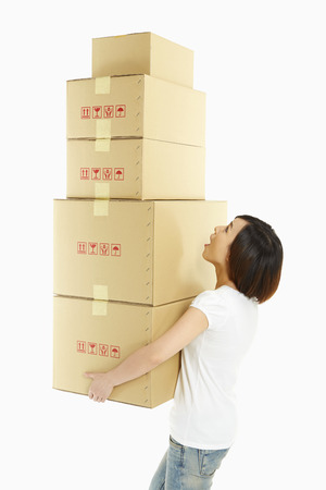 Woman carrying a stack of cardboard boxes photo