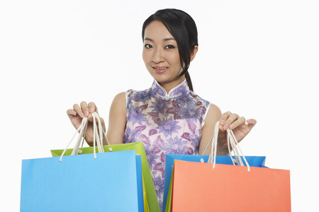 Cheerful woman in traditional clothing carrying colorful paper bags photo
