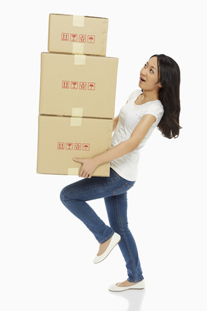 Woman carrying a stack of cardboard boxes Stock Photo - 22622616