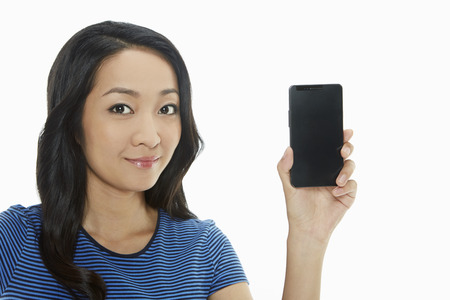 Cheerful woman holding up a mobile phone