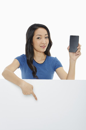 downwards: Cheerful woman holding up a mobile phone and pointing