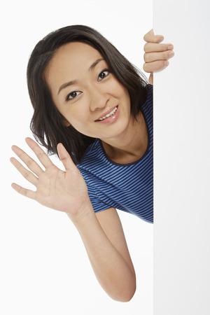 Cheerful woman waving at the camera photo