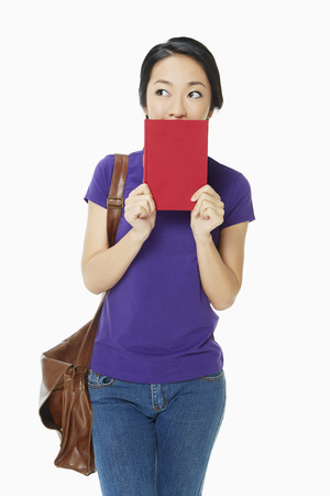 Woman covering her mouth with a book photo