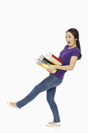 clumsy: Woman carrying a stack of books Stock Photo