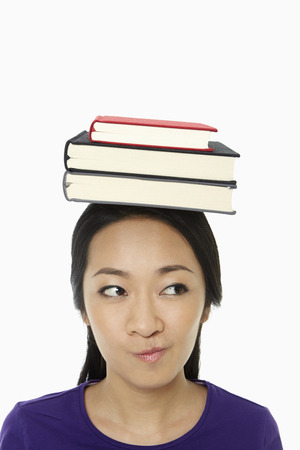 Woman with a stack of books on her head photo