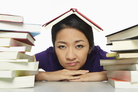 Woman surrounded by books, looking bored