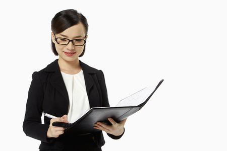 Businesswoman writing notes in folder photo