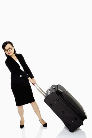 Businesswoman pulling a heavy luggage bag
