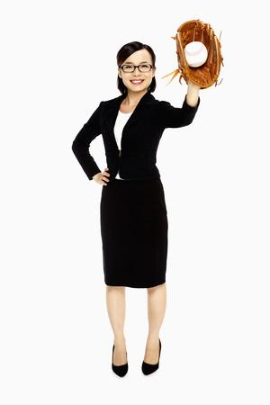 Businesswoman playing baseball