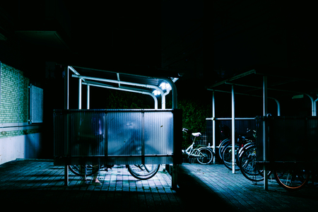 Bicycles in a lit shaded parking space at night Stock Photo