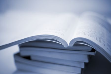 magazine stack: book accumulating on the white background. Stock Photo