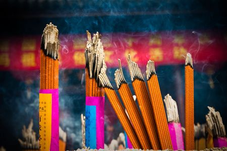 Incense sticks and candles in an Buddhist temple in Bangkok photo