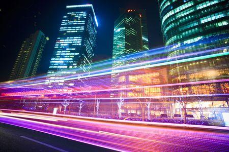 night views: the light trails on the modern building background in shanghai china. Stock Photo
