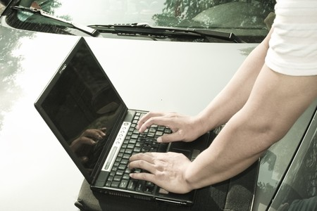 30 s: man using laptop aside the car outdoor. Stock Photo