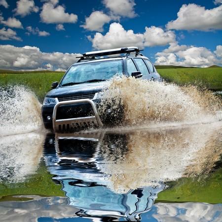SUV Splash am Fluss outdoor, Reisen auf der Straße. Lizenzfreie Bilder