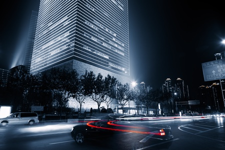city by night: the light trails on the modern building background in shanghai china. Stock Photo