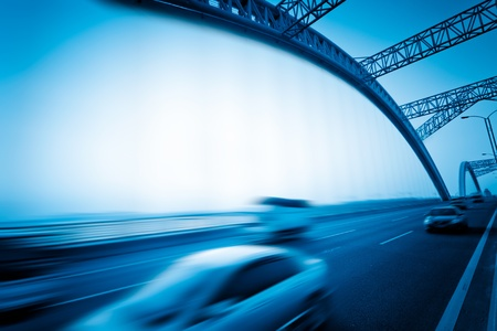cars speeding through a bridge at sunset,motion blur. photo