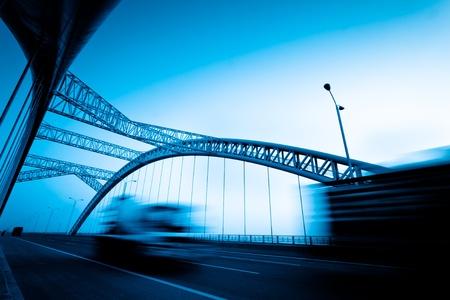 Lkw-Beschleunigung durch eine Brücke bei Sonnenuntergang, Bewegungsunschärfe.