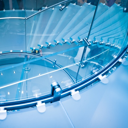 view of a staircase in a shop: Modern Glass Staircase Silhouette of walking People in shanghai china.