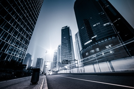 urban road: the light trails on the modern building background in shanghai china. Stock Photo