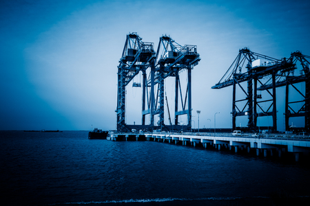 blue  toned: mechanical cranes lifting freight at pier,blue toned image.